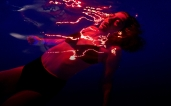 lorde in a swimming pool with neon lights from melodrama album booklet
